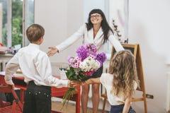 Το αγόρι και το κορίτσι δίνουν τα λουλούδια ως δάσκαλο σχολείου στο teacher& x27 ημέρα του s Στοκ Φωτογραφία