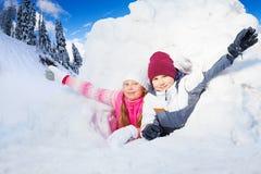 Το αγόρι και το κορίτσι ακμάζουν τα όπλα τους από μια τρύπα χιονιού Στοκ Εικόνες