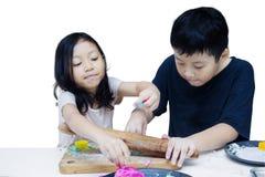 Το αγόρι και το κορίτσι κάνουν τη βιοτεχνία με το playdough Στοκ εικόνα με δικαίωμα ελεύθερης χρήσης