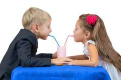Το αγόρι και το κορίτσι πίνουν το γιαούρτι. Απομονωμένος Στοκ φωτογραφίες με δικαίωμα ελεύθερης χρήσης