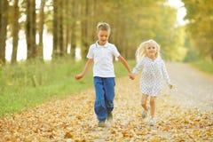 Το αγόρι και το κορίτσι πηγαίνουν χέρι-χέρι Στοκ Εικόνες