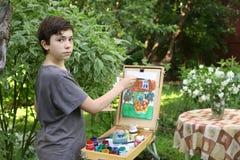 Το αγόρι καλλιτεχνών εφήβων στην εικόνα ζωγραφικής κήπων jasmin ανθίζει και του σπιτιού εξοχικών σπιτιών Στοκ φωτογραφία με δικαίωμα ελεύθερης χρήσης