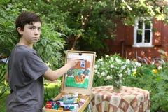 Το αγόρι καλλιτεχνών εφήβων στην εικόνα ζωγραφικής κήπων jasmin ανθίζει και του σπιτιού εξοχικών σπιτιών Στοκ Εικόνα