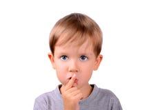 Το αγόρι καλύπτει επάνω το στόμα του με το δάχτυλο Στοκ φωτογραφία με δικαίωμα ελεύθερης χρήσης