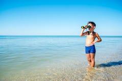 Το αγόρι κοιτάζει μέσω των διοπτρών και βλέπει τη θάλασσα Στοκ Φωτογραφίες
