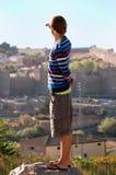 το αγόρι κοιτάζει στην πόλ&et Στοκ Φωτογραφία