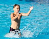 Το αγόρι κολυμπά με έναν παφλασμό στο πάρκο νερού Στοκ Φωτογραφία