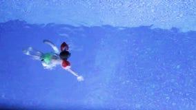Το αγόρι κολυμπά στη λίμνη με τα μανίκια το βράδυ απόθεμα βίντεο