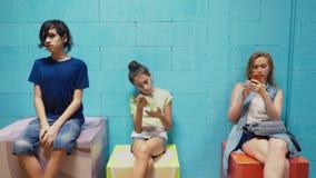 Το αγόρι, το κορίτσι και η γυναίκα χρησιμοποιούν τα κινητά τηλέφωνά τους καθμένος ενάντια στον μπλε τοίχο απόθεμα βίντεο