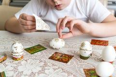 Το αγόρι κολλά τις αυτοκόλλητες ετικέττες στα αυγά Πάσχας Στοκ Φωτογραφία