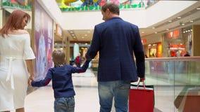 Το αγόρι κρατά ένα χέρι από τη μητέρα και τον πατέρα Συσκευασίες Sousse γονέων όχι με τα δώρα Χριστουγέννων Οικογενειακά Χριστούγ φιλμ μικρού μήκους