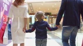 Το αγόρι κρατά ένα χέρι από τη μητέρα και τον πατέρα Συσκευασίες Sousse γονέων όχι με τα δώρα Χριστουγέννων Οικογενειακά Χριστούγ απόθεμα βίντεο