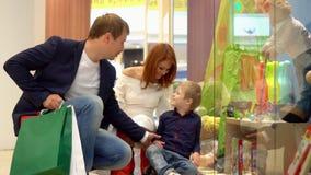 Το αγόρι κρατά ένα χέρι με τον πατέρα Ο πατέρας αντέχει τις συσκευασίες με τα δώρα Χριστουγέννων Αγορές οικογενειακών Χριστουγένν φιλμ μικρού μήκους