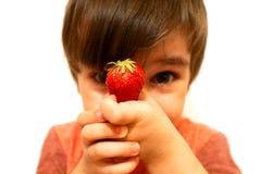 Το αγόρι κρατά στο χέρι του μια κόκκινη φράουλα στοκ εικόνα