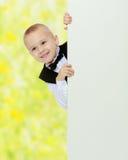 Το αγόρι κρυφοκοιτάζει έξω από πίσω από το έμβλημα Στοκ εικόνα με δικαίωμα ελεύθερης χρήσης