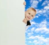 Το αγόρι κρυφοκοιτάζει έξω από πίσω από το έμβλημα Στοκ Εικόνα