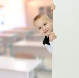 Το αγόρι κρυφοκοιτάζει έξω από πίσω από το έμβλημα Στοκ φωτογραφίες με δικαίωμα ελεύθερης χρήσης