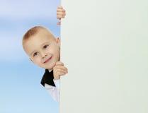 Το αγόρι κρυφοκοιτάζει έξω από πίσω από το έμβλημα Στοκ Φωτογραφία