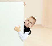 Το αγόρι κρυφοκοιτάζει έξω από πίσω από το έμβλημα Στοκ εικόνες με δικαίωμα ελεύθερης χρήσης