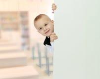 Το αγόρι κρυφοκοιτάζει έξω από πίσω από το έμβλημα Στοκ Φωτογραφίες