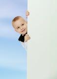 Το αγόρι κρυφοκοιτάζει έξω από πίσω από το έμβλημα Στοκ Εικόνες