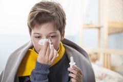 Το αγόρι κρυώνει και φυσά τη μύτη της στο σπίτι στοκ φωτογραφίες