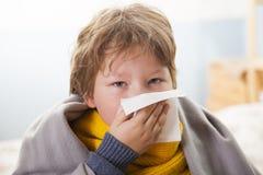 Το αγόρι κρυώνει και φυσά τη μύτη της στο σπίτι στοκ εικόνα με δικαίωμα ελεύθερης χρήσης