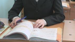Το αγόρι κτυπά τις σελίδες του εγχειριδίου στο σχολείο φιλμ μικρού μήκους