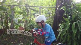 Το αγόρι μαθαίνει να οδηγά ένα ποδήλατο με την πλήρη προστασία με τη φλόγα ήλιων φιλμ μικρού μήκους