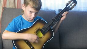 Το αγόρι μαθαίνει να παίζει τη συνεδρίαση κιθάρων στον καναπέ Έννοια της εκμάθησης να παίζεται ένα μουσικό όργανο φιλμ μικρού μήκους