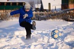 Το αγόρι μαθητών κλωτσά το παιχνίδι σφαιρών στο χειμερινό ποδόσφαιρο στο s στοκ φωτογραφία με δικαίωμα ελεύθερης χρήσης