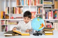 Το αγόρι μελετά τη σφαίρα και διαβάζει το βιβλίο Στοκ φωτογραφία με δικαίωμα ελεύθερης χρήσης