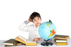 Το αγόρι μελετά τη σφαίρα και διαβάζει το βιβλίο Στοκ φωτογραφίες με δικαίωμα ελεύθερης χρήσης