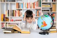 Το αγόρι μελετά τη σφαίρα και διαβάζει το βιβλίο Στοκ Εικόνες
