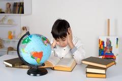 Το αγόρι μελετά τη σφαίρα και διαβάζει τα βιβλία Στοκ φωτογραφία με δικαίωμα ελεύθερης χρήσης