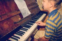 Το αγόρι μελετά τις χορδές στις σημειώσεις, καθμένος στο πιάνο Στοκ φωτογραφία με δικαίωμα ελεύθερης χρήσης