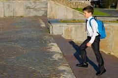 Το αγόρι με ένα μπλε σακίδιο πλάτης πίσω από τον, μετά από το σχολείο, αναρριχείται στα σκαλοπάτια στην κορυφή στοκ εικόνα