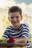 Το αγόρι με αυξήθηκε σε έναν πίνακα στον καφέ οδών Στοκ Εικόνες
