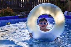Το αγόρι με τα γυαλιά για την κολύμβηση στη λίμνη κολυμπά με έναν διογκώσιμο κύκλο στοκ φωτογραφία με δικαίωμα ελεύθερης χρήσης