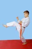 Το αγόρι με την πορτοκαλιά ζώνη κτύπησε το πόδι λακτίσματος Στοκ φωτογραφία με δικαίωμα ελεύθερης χρήσης