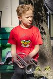 Το αγόρι με τη σάλπιγγα κάθεται στον πάγκο στην οδό στοκ εικόνες