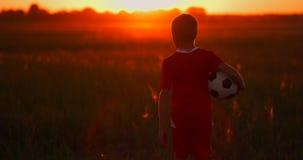 Το αγόρι με τη σφαίρα στο ηλιοβασίλεμα πηγαίνει στον ήλιο και κοιτάζει φιλμ μικρού μήκους