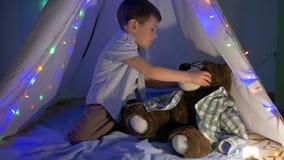 Το αγόρι με τη teddy αρκούδα έχει το χρόνο διασκέδασης στο ντεκόρ σκηνών με τη γιρλάντα στο σπίτι το βράδυ φιλμ μικρού μήκους