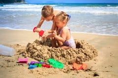 Το αγόρι μικρών κοριτσιών στηρίζεται την άμμο Castle από την κυματωγή κυμάτων στην παραλία Στοκ Εικόνες