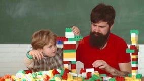 Το αγόρι μικρών παιδιών σε ένα πορτοκαλί κράνος ή το κράνος βοηθά το γενειοφόρο πατέρα του Παιδάκι και το σπίτι οικοδόμησης πατέρ απόθεμα βίντεο