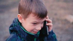 Το αγόρι μιλά σε ένα κινητό τηλέφωνο στο πάρκο και γελά Μπροστινή άποψη, κινηματογράφηση σε πρώτο πλάνο προσώπου απόθεμα βίντεο