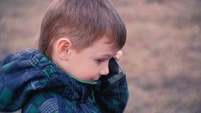 Το αγόρι μιλά σε ένα κινητό τηλέφωνο στο πάρκο Πρόσωπο κινηματογραφήσεων σε πρώτο πλάνο, πλάγια όψη απόθεμα βίντεο