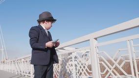 Το αγόρι μοιάζει με έναν επιχειρηματία σπαταλά και ρίχνει τα χρήματα στον αέρα από τη γέφυρα απόθεμα βίντεο