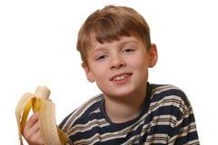 το αγόρι μπανανών τρώει στοκ φωτογραφίες