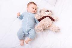 Το αγόρι νηπίων που βρίσκονται στο κρεβάτι και η αρπαγή teddy αντέχουν Στοκ εικόνες με δικαίωμα ελεύθερης χρήσης